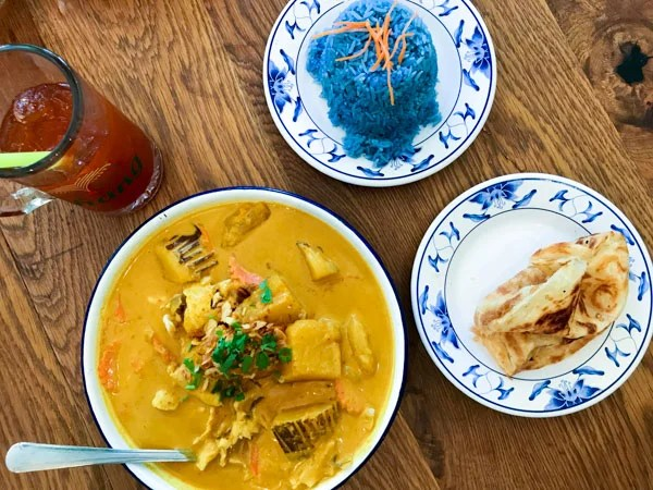 Thai Farmhouse Kitchen lunch menu items yellow curry with potato, onion, crispy shallot and chicken with a side of roti and blue rice