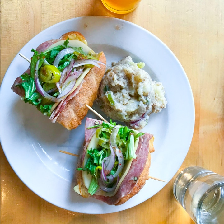 olympia provisions lunch menu item italian sandwich on a table with beer in portland