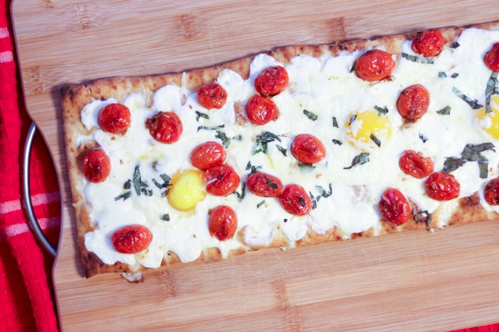 Baked breakfast pizza with eggs and tomatoes on a cutting board