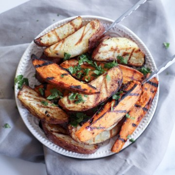 grilled potato wedges with tongs on a gray table