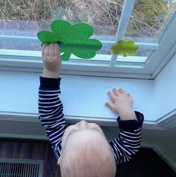 Simple Ways To Decorate For St Patrick's Day including window clings and a baby by a window