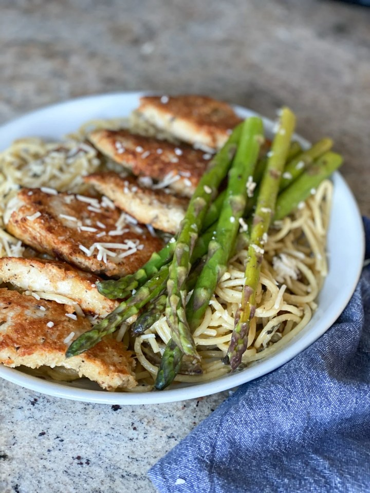 sous vide asparagus plated with chicken parmesan
