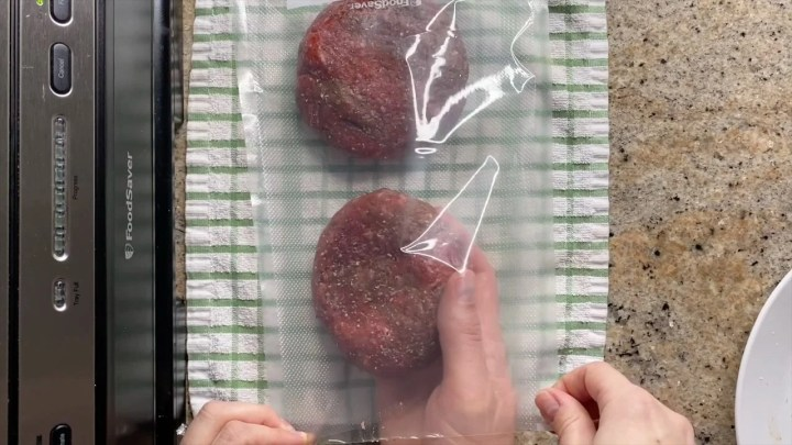 putting burgers in vacuum sealed bags to freeze them
