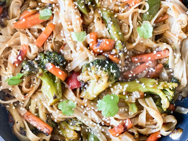 closeup of stir fry with carrots, broccoli, rice noodles, cilantro and sesame noodles