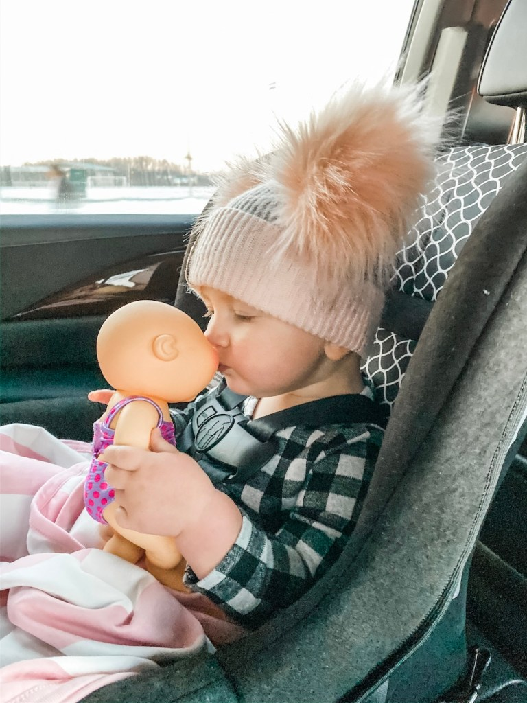 Baby sitting in carseat kissing baby doll