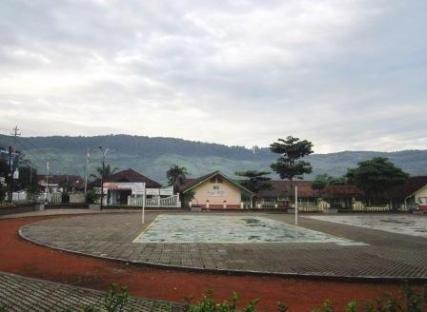 Taman dg latar belakang Balai Desa dan sebuah sekolah dasar