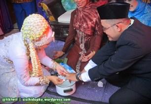 Sang istri membersihkan jari tangan suami.
