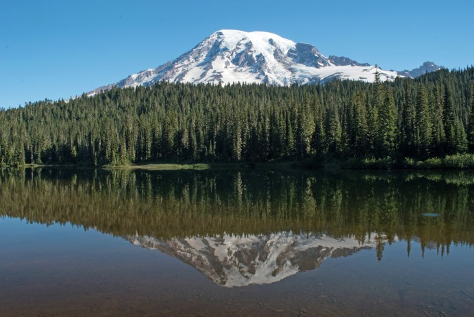 A snow-capped mountain peeking out above a forest, reflecting in a lake.