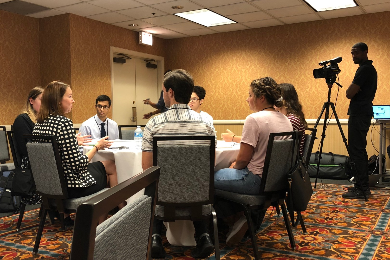 Six students sit around a round table in a conference room, in discussion, and someone is filming them