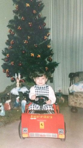 A young child sits in a toy car, gripping the wheel, indoors in front of a Christmas tree.