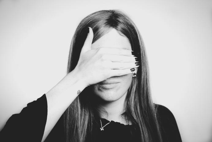 Grayscale photo of a white woman covering her eyes with her hand.