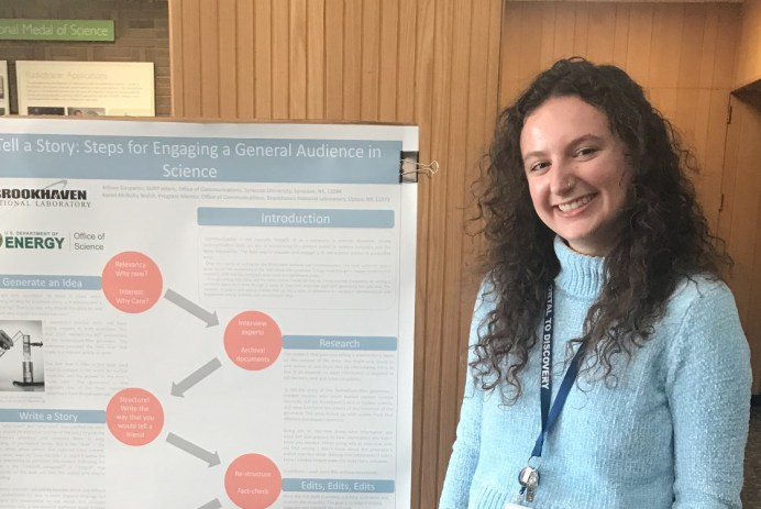 """A smiling person (with curly hair, a blue sweater, and a lanyard around her neck) stands next to a poster with the title """"Tell a story: steps for engaging a general audience in science"""""""
