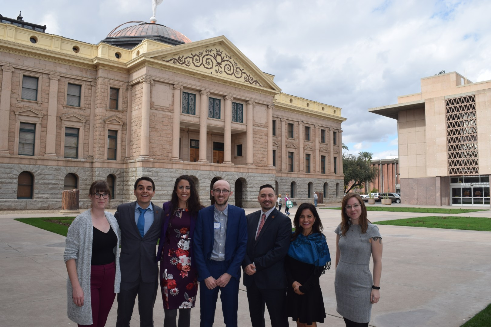 A group of 7 people in business attire standing outside in front of the Arizona state capitol building.