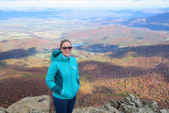 A person in a aqua-colored outdoor jacket and sunglasses stands with a beautiful overlook behind her.