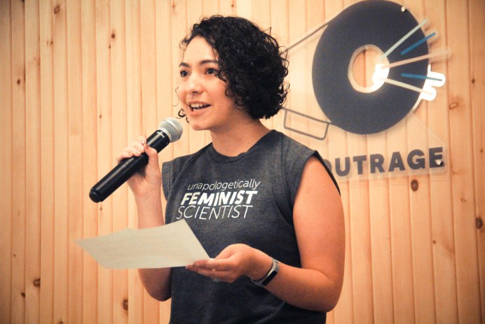 "Jewel speaks into a microphone with a wood-paneled wall and a sign that says ""The Outrage"" behind her. She is wearing a shirt that says ""unapologetically feminist scientist."""