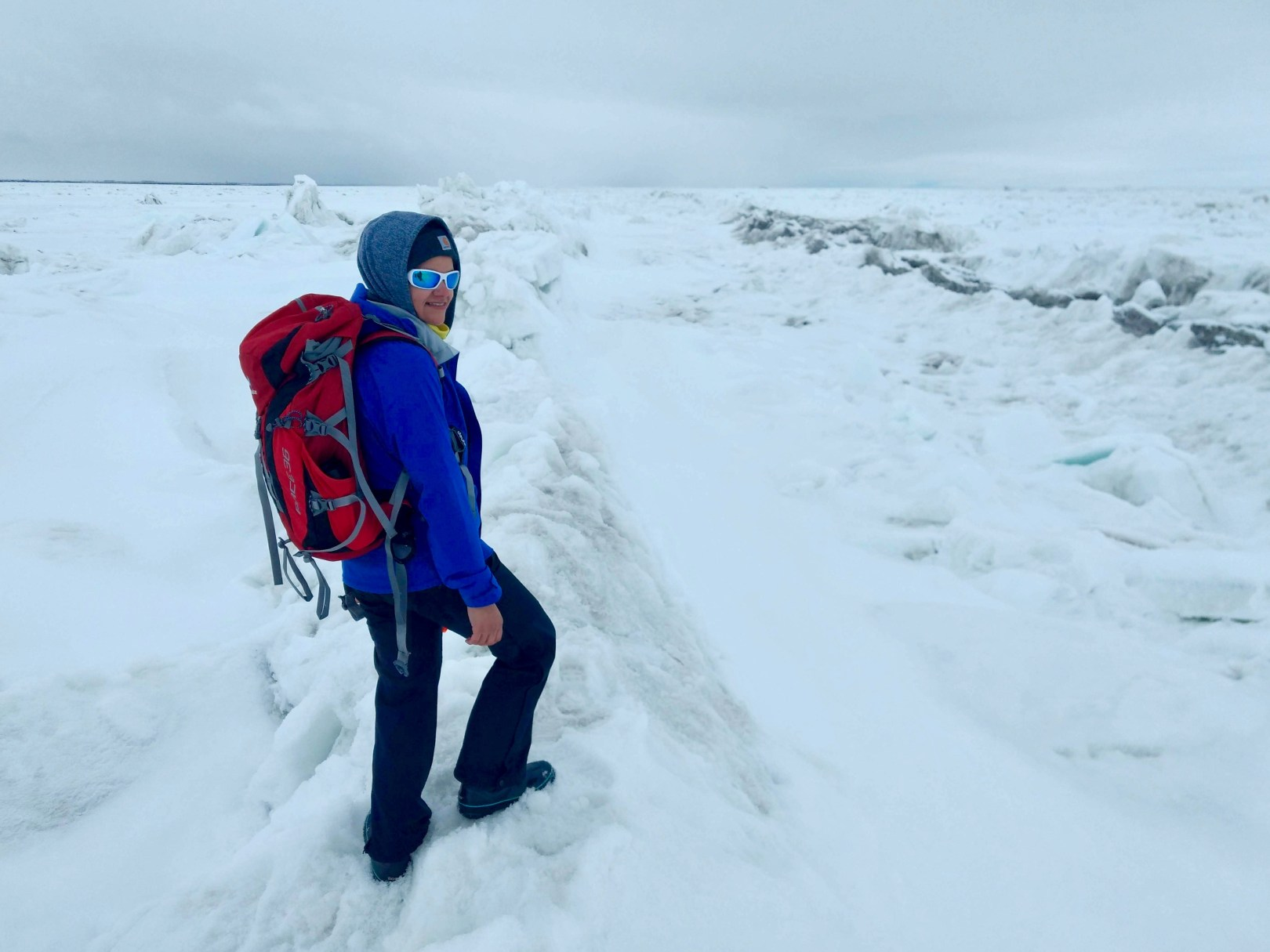 Dina Abdel-Fattah standing on sea ice pressure ridge. She is bundled up in snow/ice gear, is wearing a big red backpack, and is stepping on snow. There is white snow/ice as far as the eye can see.