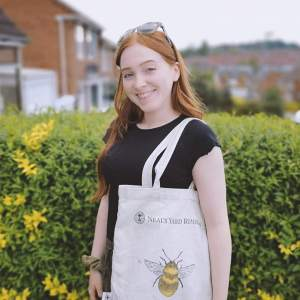 The author is smiling, standing outside with a black shirt, canvas bag with a bee on it, and sunglasses on her head. There is a bush with yellow flowers and brick buildings in the background.