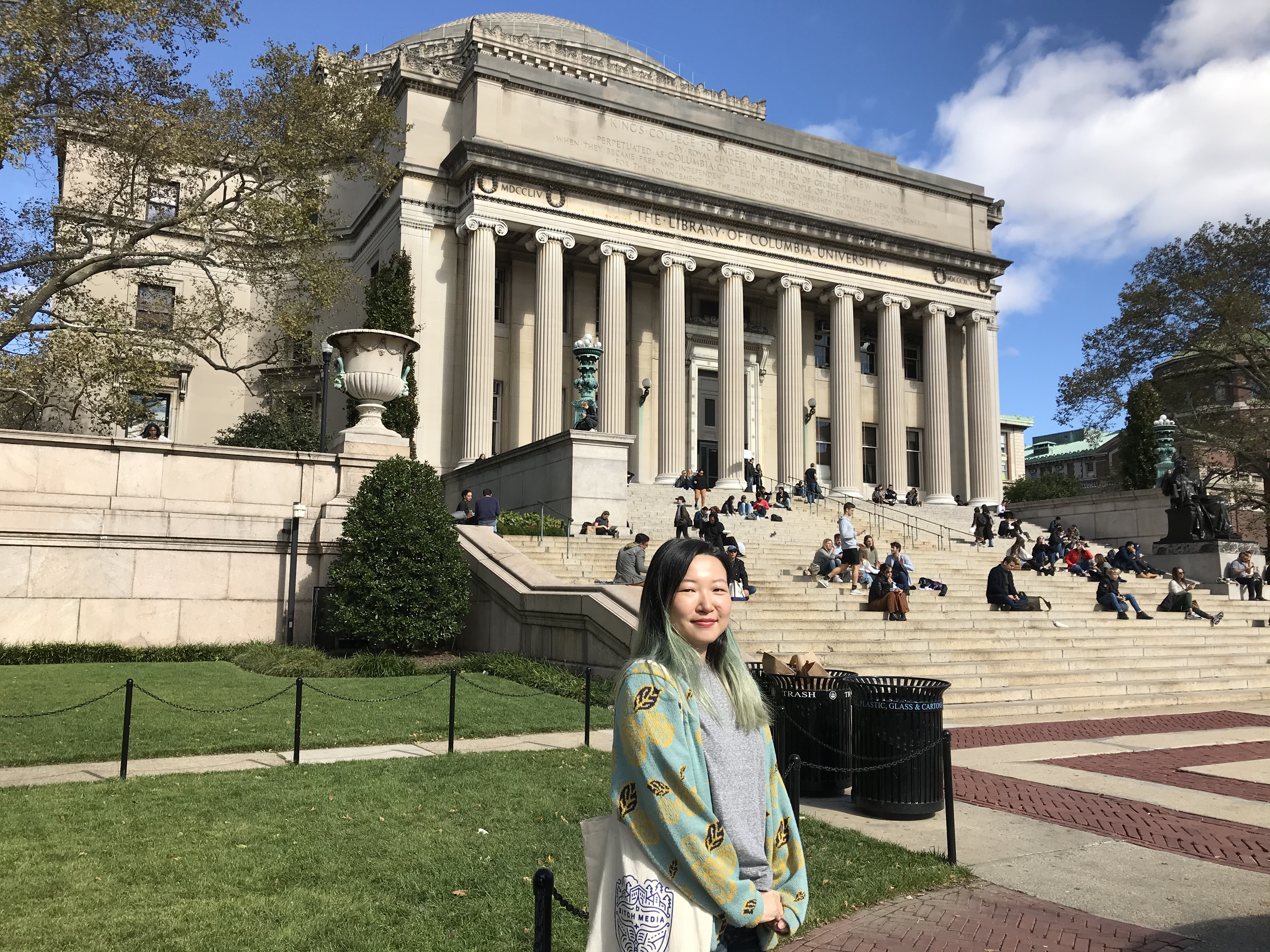 The author is standing in front of a building with columns and marble steps with students sitting on them. It looks like an academic campus.