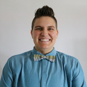 The author is smiling, has short spiked hair, and is wearing a blue button-down and bow-tie.