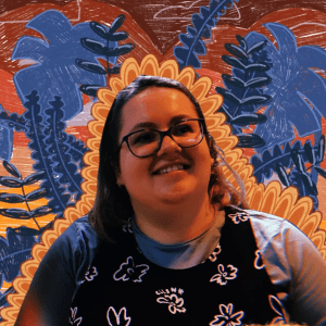 Close-up of the author wearing glasses and smiling in front of a colorful background that looks like an art mural.