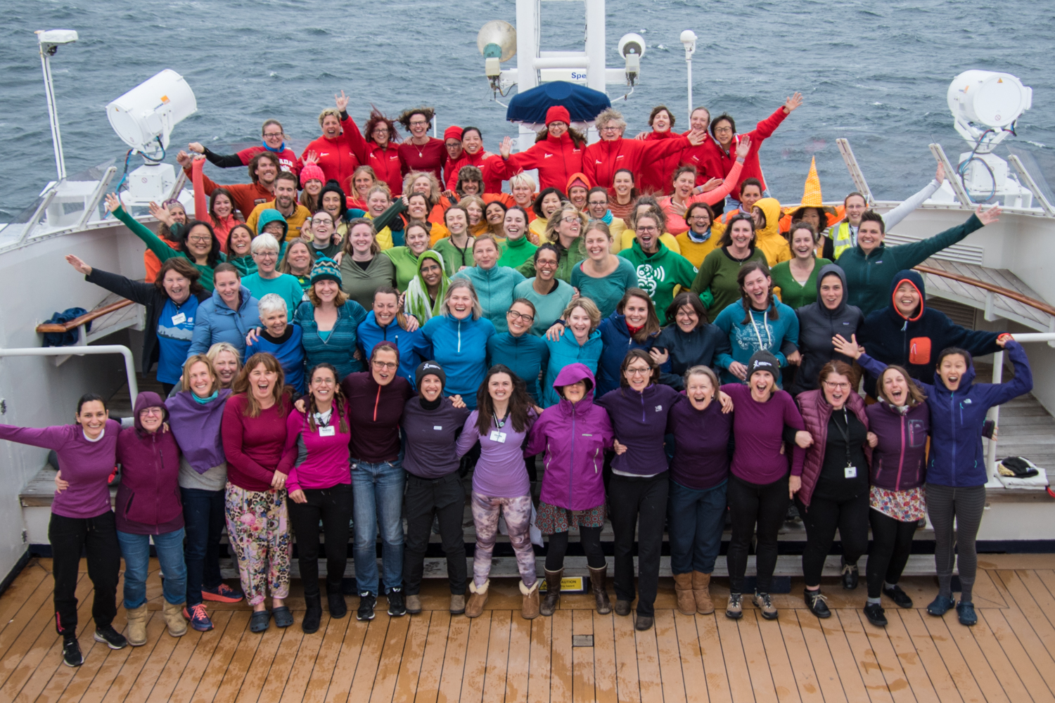 Women scientists form a human pride flag, forming 6 rows of rainbow stripes on the bow of a boat with their different colored clothing. The people are smiling, some with their arms triumphantly up. There is wavy grey water in the background.