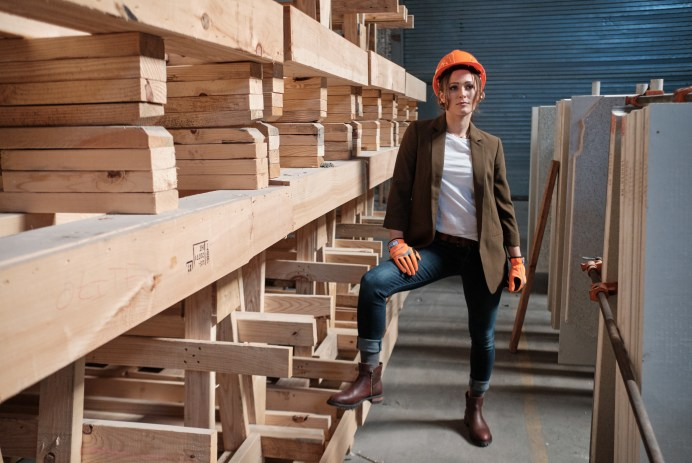 A woman wearing a hardhat, safety gloves, and Juno Jones shoes poses confidently among wood boards at a construction site.