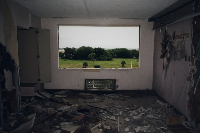 A room in ruins with a broken window showing lush green foliage.