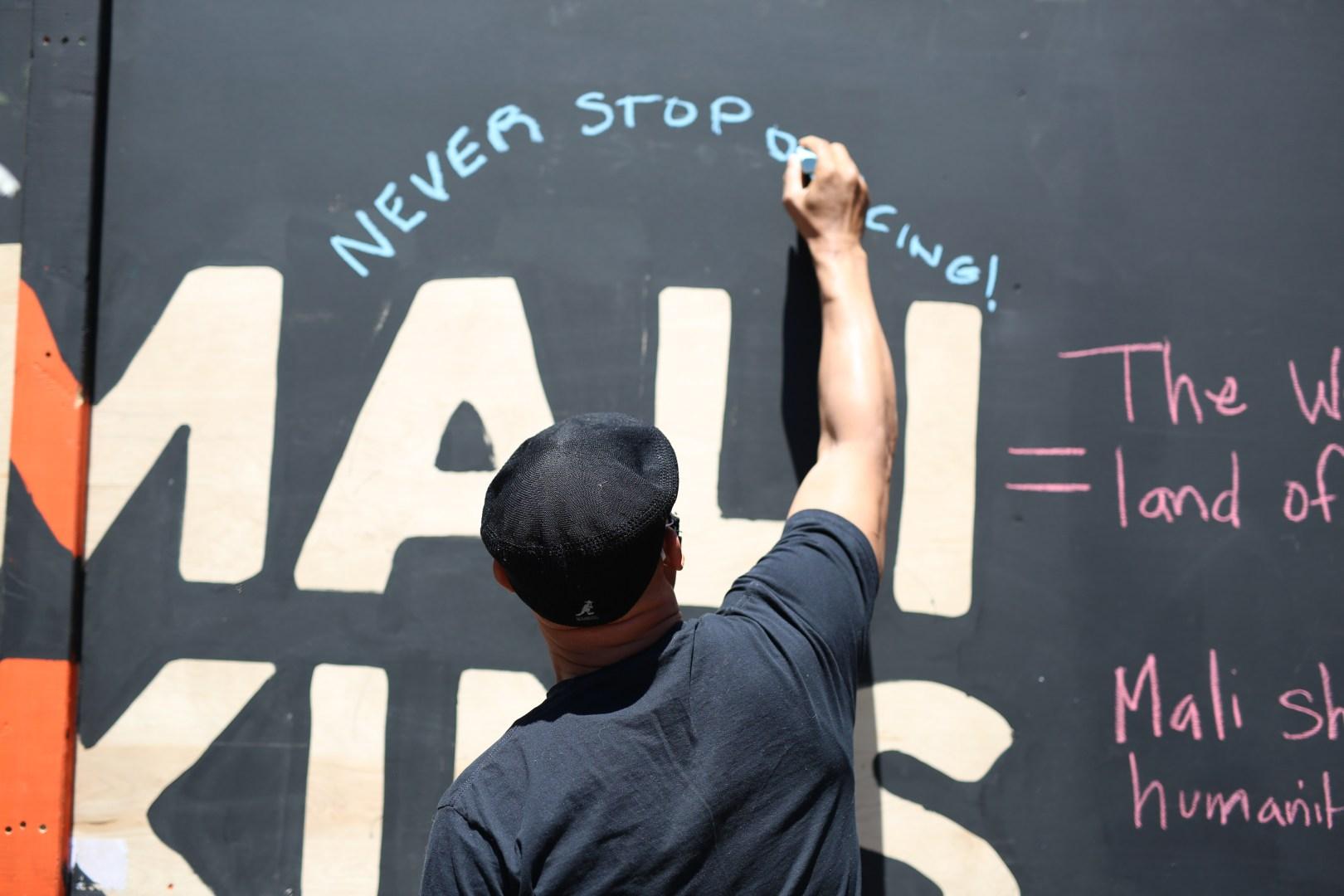 Man writes on interactive art installation dedicated to Mali Watkins and Black Lives Matter. Photo courtesy of Walter Wallace.