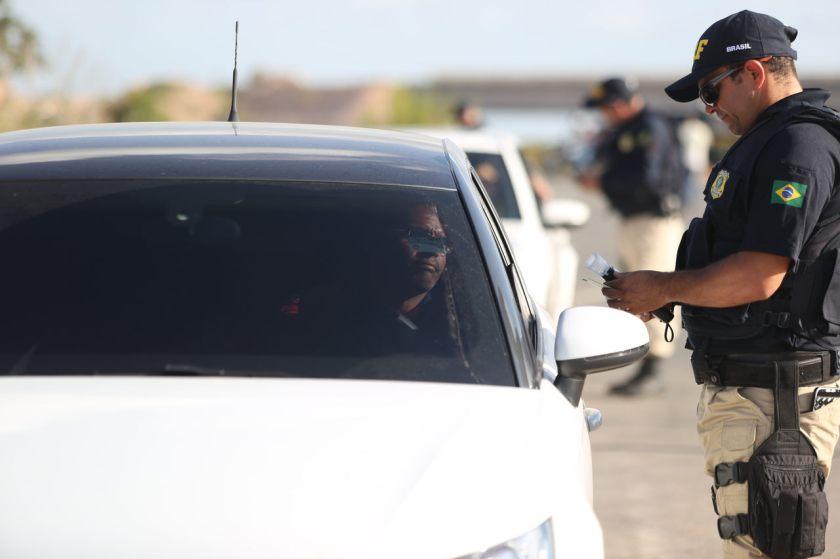 policial rodoviario federal para motorista de carro branco em rodovia