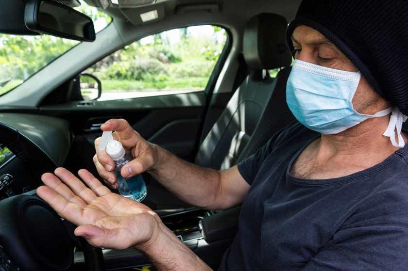homem motorista despeja alcool em gel em sua mão