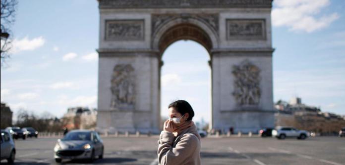 Uma mulher usando uma máscara protetora caminha perto do Arco do Triunfo enquanto a França enfrenta um surto de doença por coronavírus, em Paris