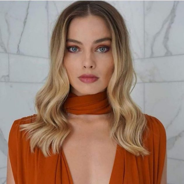 Margot Robie usando look laranja