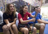 Amber Schnepp '21, Nerissa Barling '21, and Case Osborn '21 take a break from the rock climbing wall to watch others during a Bridge Scholars outing to the CC climbing gym. Photo by Jennifer Coombes