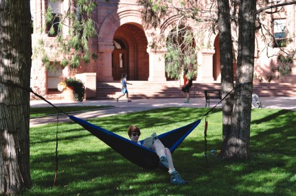 A student reads in a hammock outside Palmer Hall on a beautiful day.