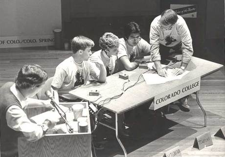 Simons consults with CC students, including Jon-Mark Colwell Patterson '89, Stephanie Vignoul Owens '88, and Marc Towersap '87, at the College Bowl, October 1987.