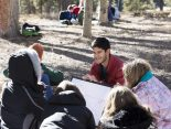 """Nathan Agarwal '19 reviews a lesson on global warming with students in the shade of the trees at the Catamount Center during the winter ecology part of the semester. """"Teaching them about this is so important, """" said Julie Francis, executive director of the Catamount Center. """"They are our future and hopefully they will be able to vote and make a change in the future."""""""