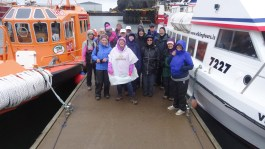 Group photo returning from a rainy boat trip around Heimaey volcanic island, where a 1973 eruption buried one-quarter of the town.