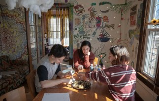Lily Epstein '22, Abby Gray '21 and Liza Scher '22 sit at the dining room table at Synergy House where they talk over plans for break and taste test Scher's latest culinary experiment, roasted artichokes with lemon aioli. Students at the houses are encouraged to make the space their own and to embrace living in community.