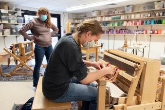 Frances Heiss '15 instructs a weaving class in the Arts and Crafts Center, teaching techniques to Sarah Edell '24. Photo by Chidera Ikpeamarom '22