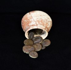 The collection of ancient bronze coins, discovered in this small ceramic jar, discovered in Area 20 of Shikhin, Field I. Photo Credit: Steve Meigs