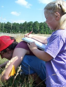 Teamwork in the field. Hannah Bernhardt records data while Bonnie McGill identifies plant species in a NC old field.
