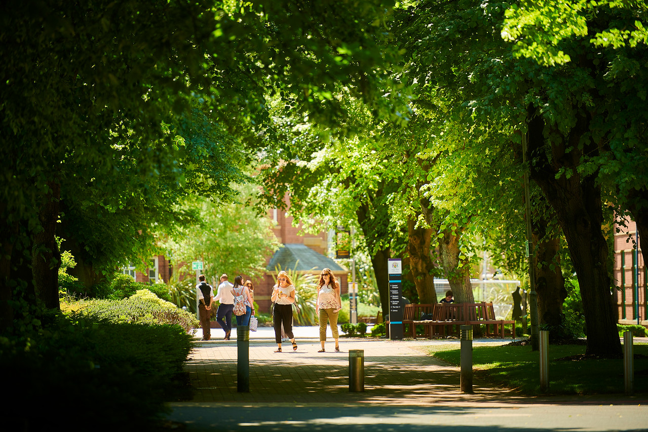 2 students walking through campus on a sunny day