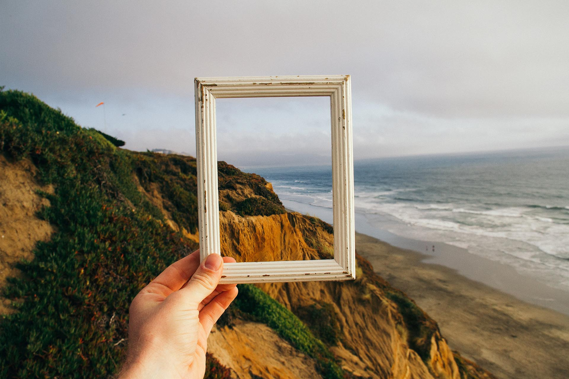 Hand holding a wooden frame in front of a cliff and beach landscape