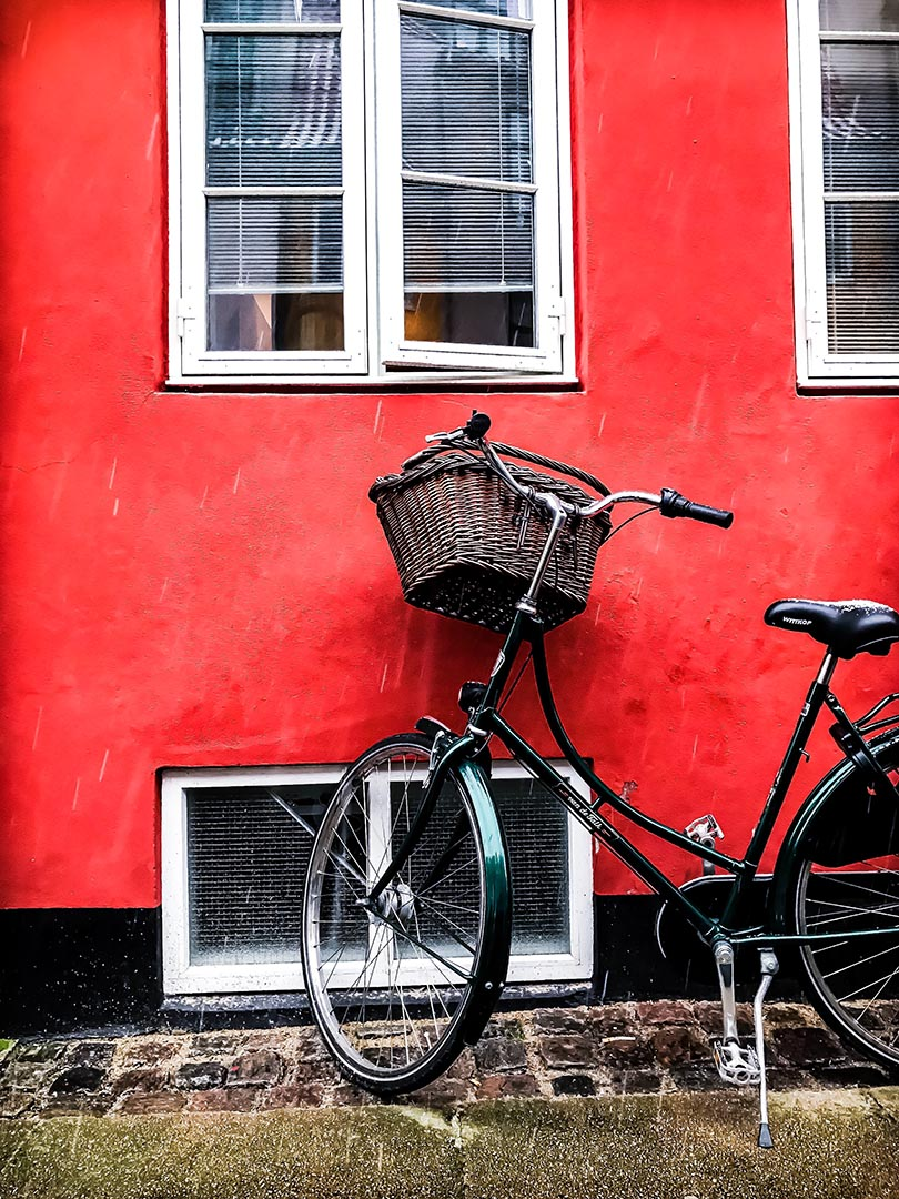 Bicycle lent against a red house in Copenhagen