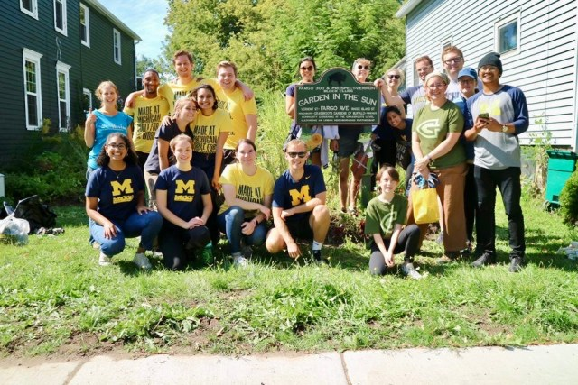 """Students wearing Michigan shirts gather in front of a garden with a sign """"Garden in the Sun""""."""