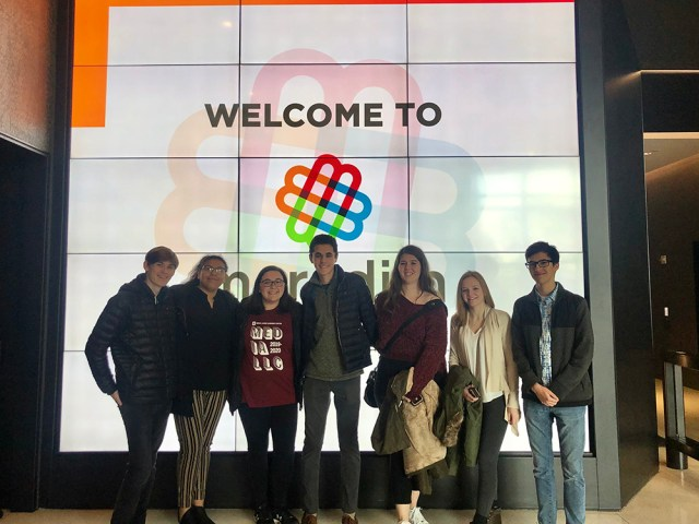 Media LLC Students pose in front of a digital screen in the Meredith lobby