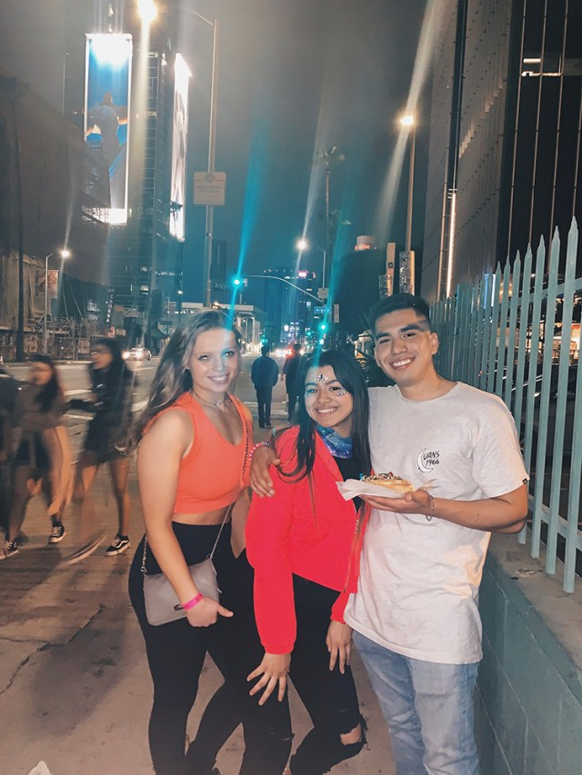 Three students on a street in L.A. at night