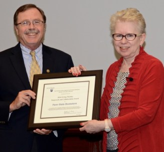 woman, standing, presenting framed certificate to man, also standing