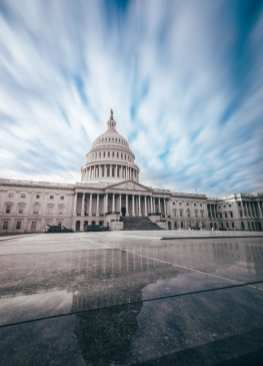 U.S. Capitol building with blurred clouds above.