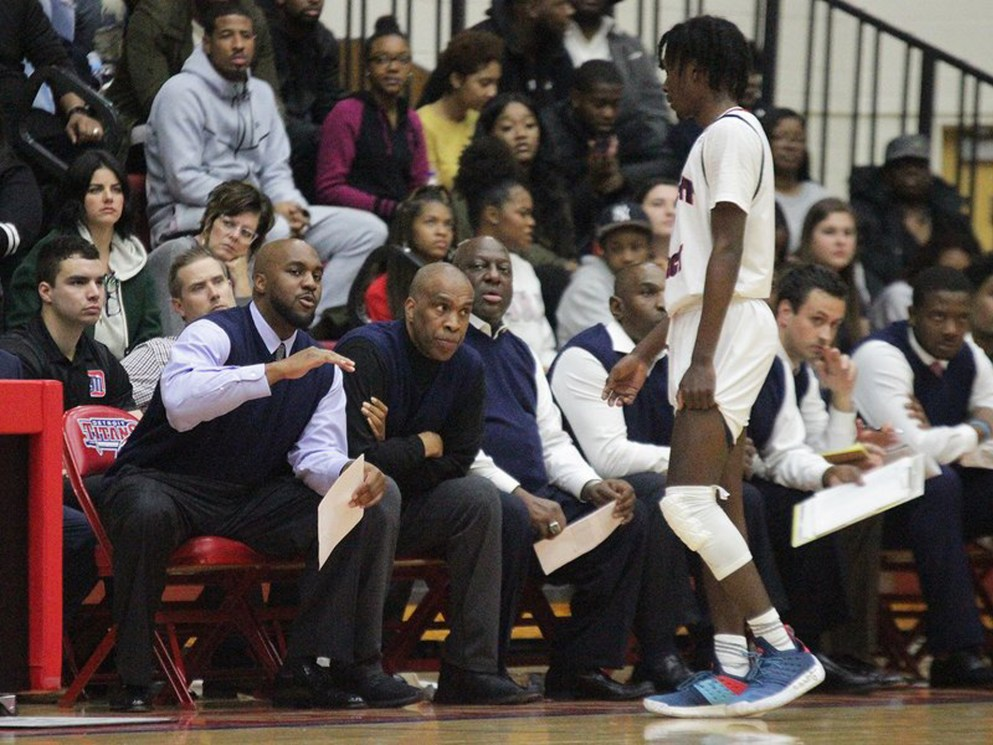 Mike Davis Jr., left, and his father, center, talk with Antoine Davis at a recent game.